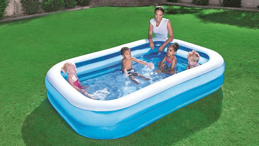 Vier Kinder spielen in einem aufgeblasenen Pool von Bestway. Eine Frau steht daneben