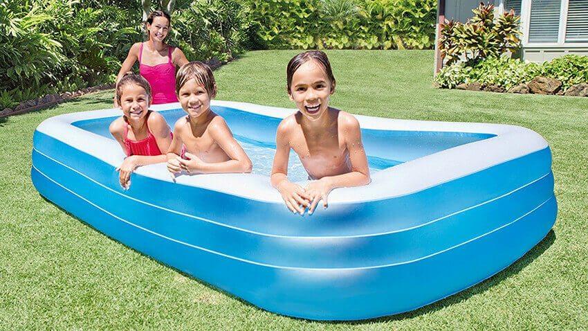 Blauer viereckiger aufgeblasener Pool in dem 3 Kinder spielen. Daneben steht eine Frau und passt auf.