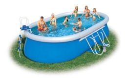 Bild zeigt großen pool auf grüner Wiese. Darin schwimmen sieben Menschen