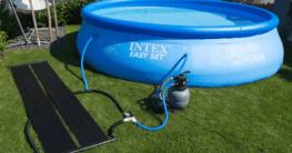 Das Bild zeigt einen Pool mit einer Solar-Heizung, die neben dem Pool liegt. Beide sind mittels Schlauch miteinander verbunden