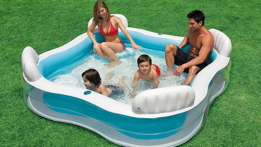 Quadratischer Pool mit Wasser gefüllt. Darin sitzen zwei Erwachsene in der Ecke und zwei Kinder planschen im Wasser