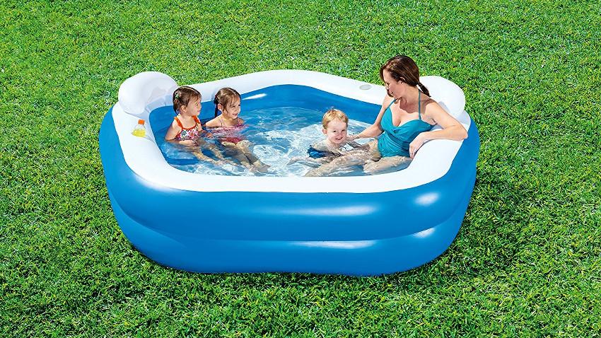 kleiner Pool auf grünem Rasen. Darin sitzen eine Frau und drei Kinder