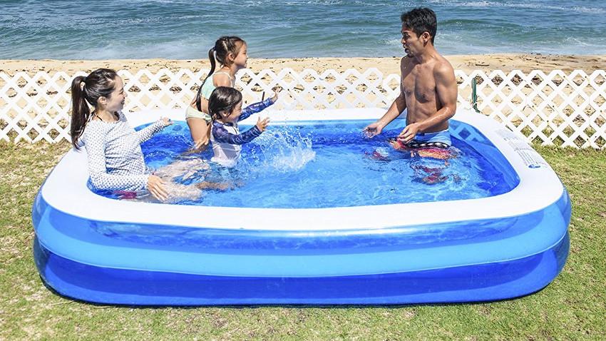 rechtekiger Pool steht in einem Garten auf grünem rasen. Darin planscht eine Familie
