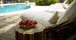 Sonnenliege mit weißem Bezug steht vor einem türkisfarbenem Pool